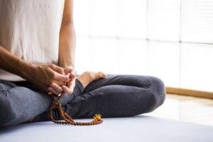 Donna che pratica meditazione con un mala in mano - mindfulness